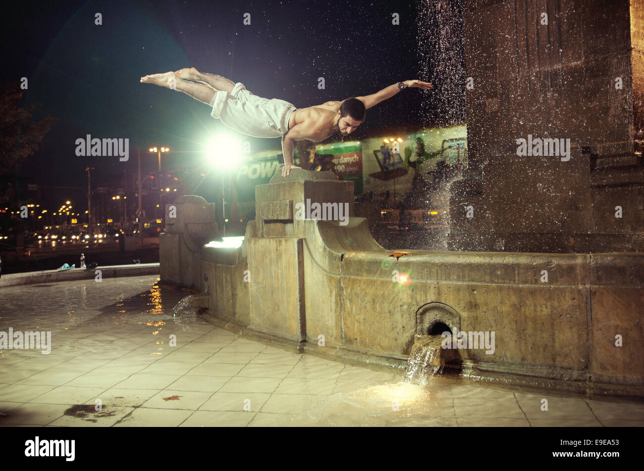 Muscular guy doing push-ups in a fountain - Stock Image
