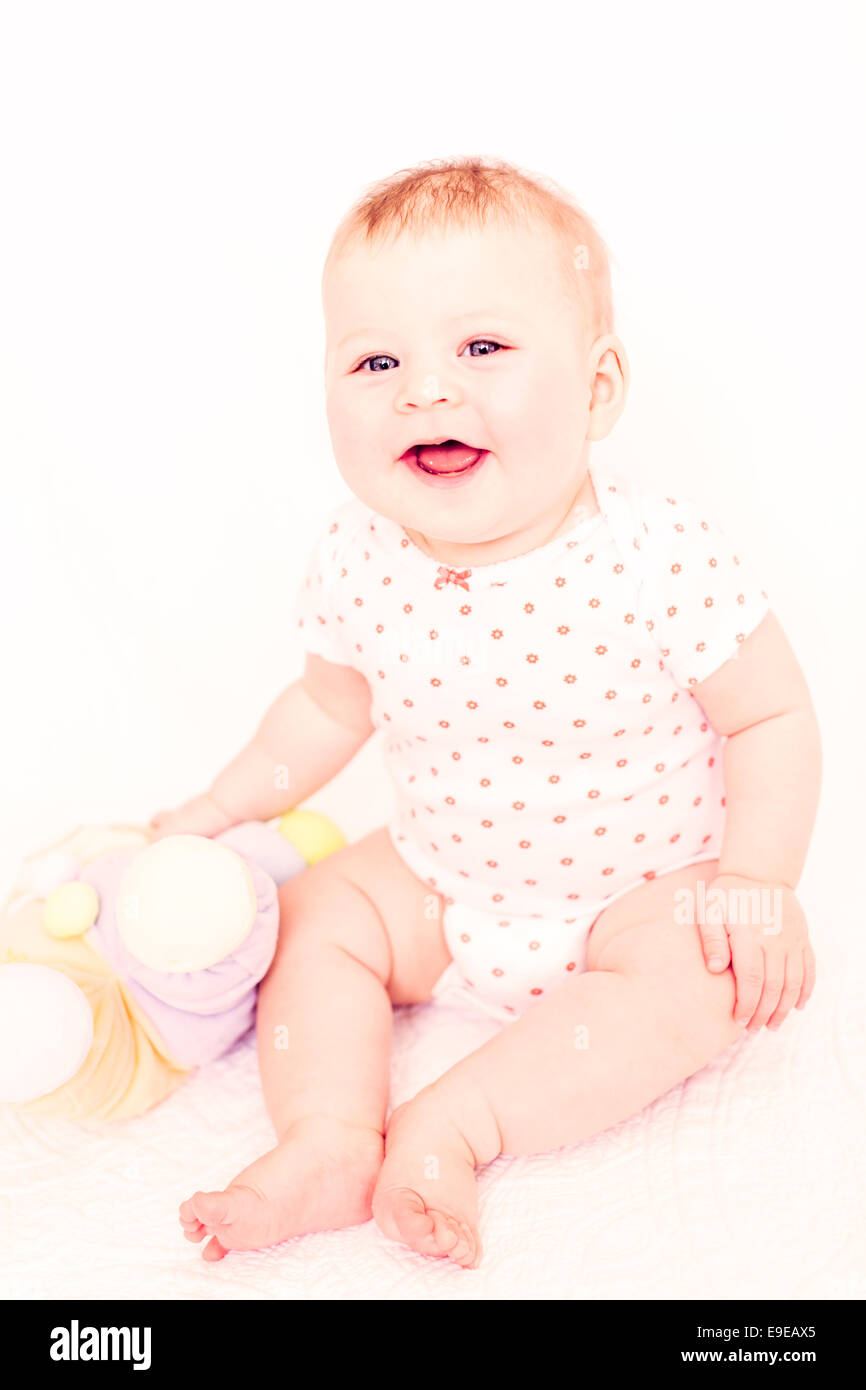Cute baby girlplaying on a white blanket. - Stock Image