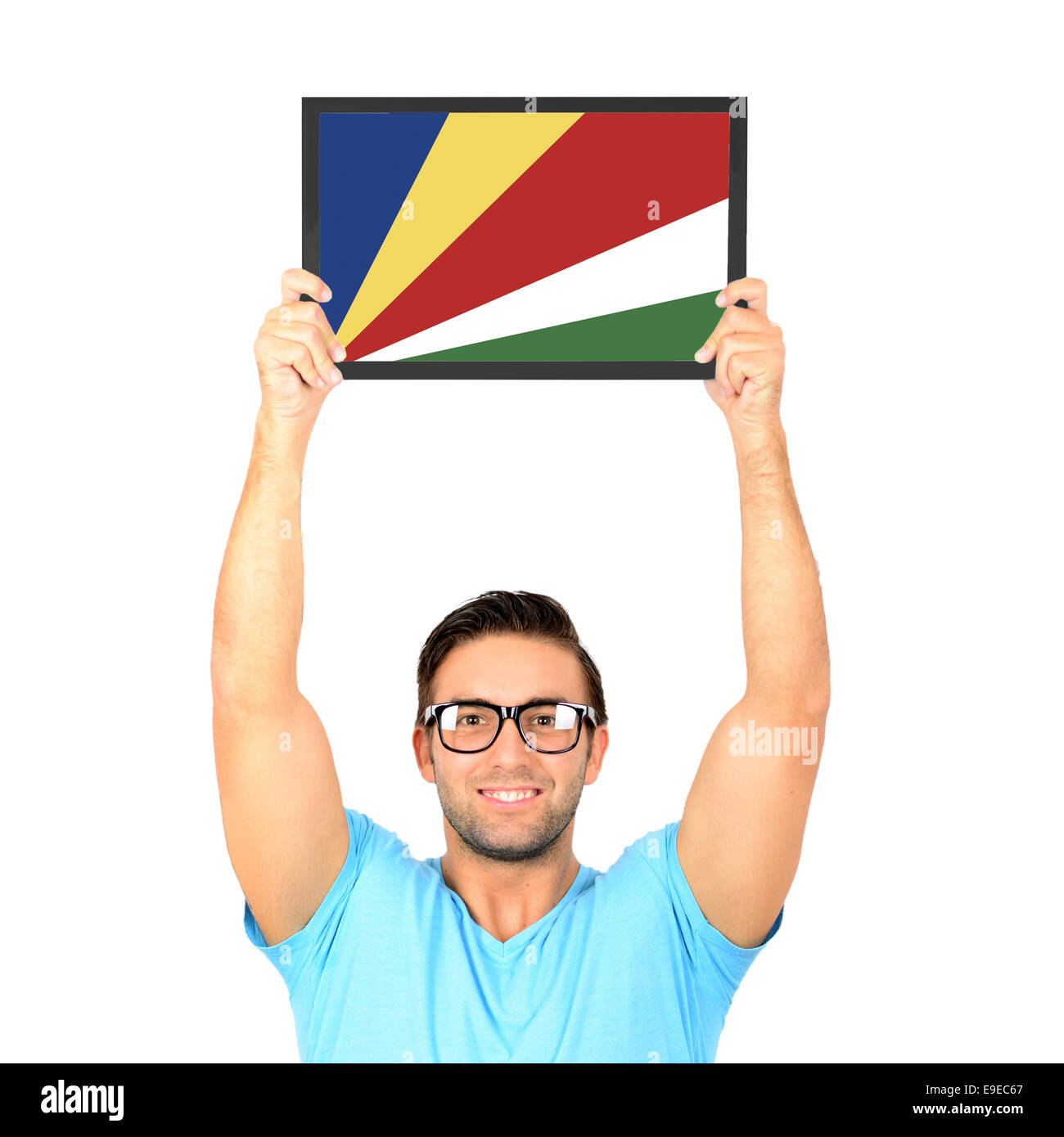 Portrait of a young casual man holding up board with National flag of Seychelles - Stock Image