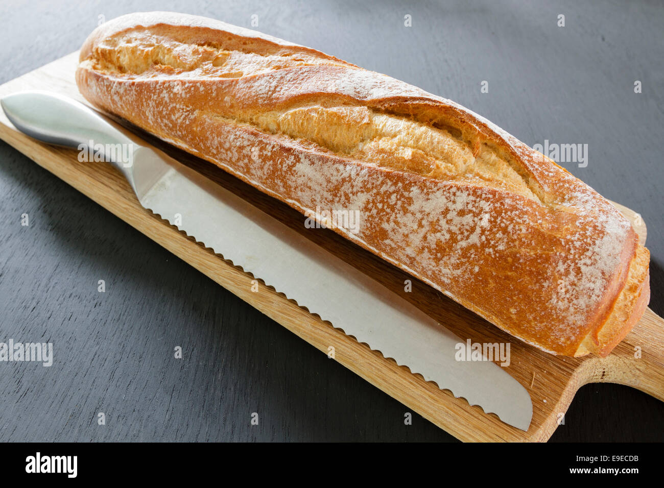 Fresh crusty baguette next to a bread knife on a wooden chopping board - Stock Image
