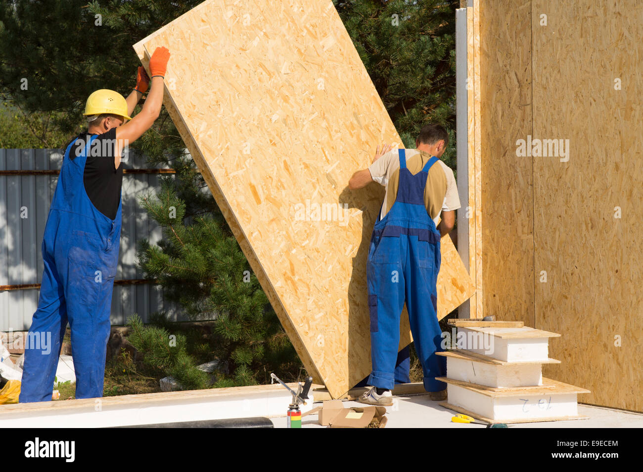 Construction workers positioning timber wall panels in a new build ...