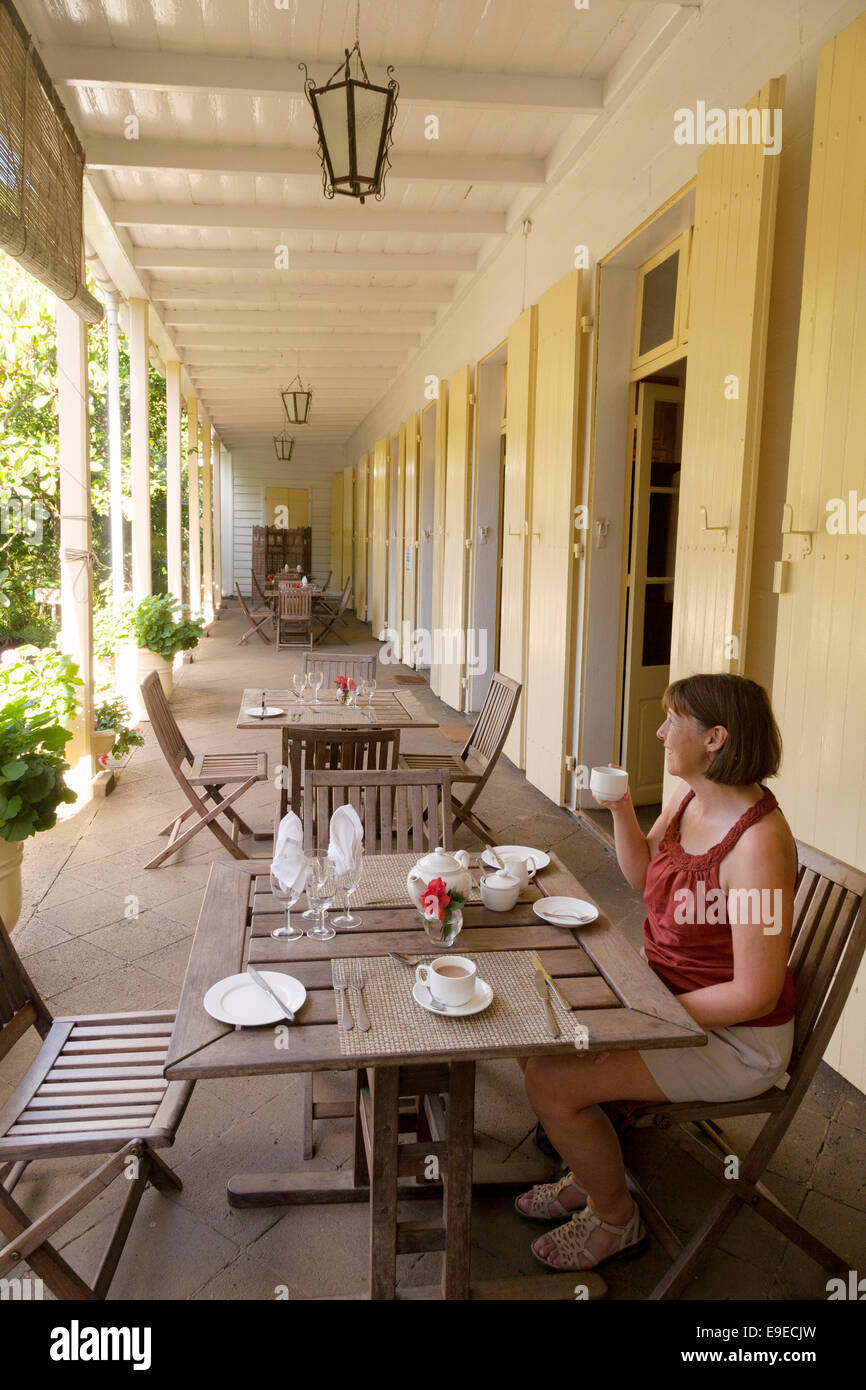 A tourist having tea on the veranda, Eureka House, a 19th century creole house; Mauritius - Stock Image