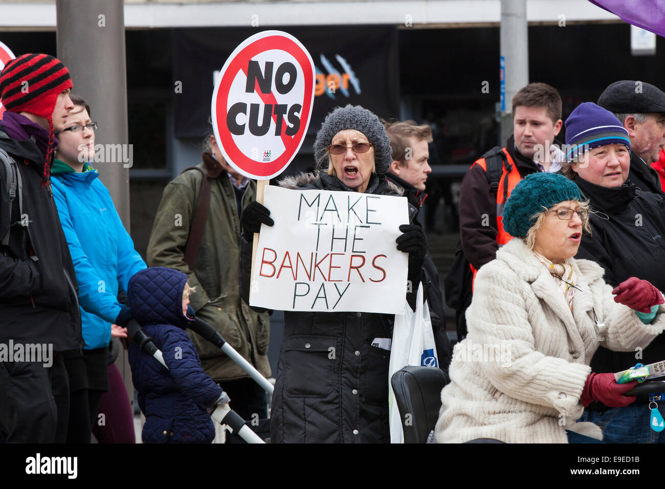A woman holds a placard reading 'no cuts' and a sign reading 'make the bankers pay. at an anti-austerity - Stock Image