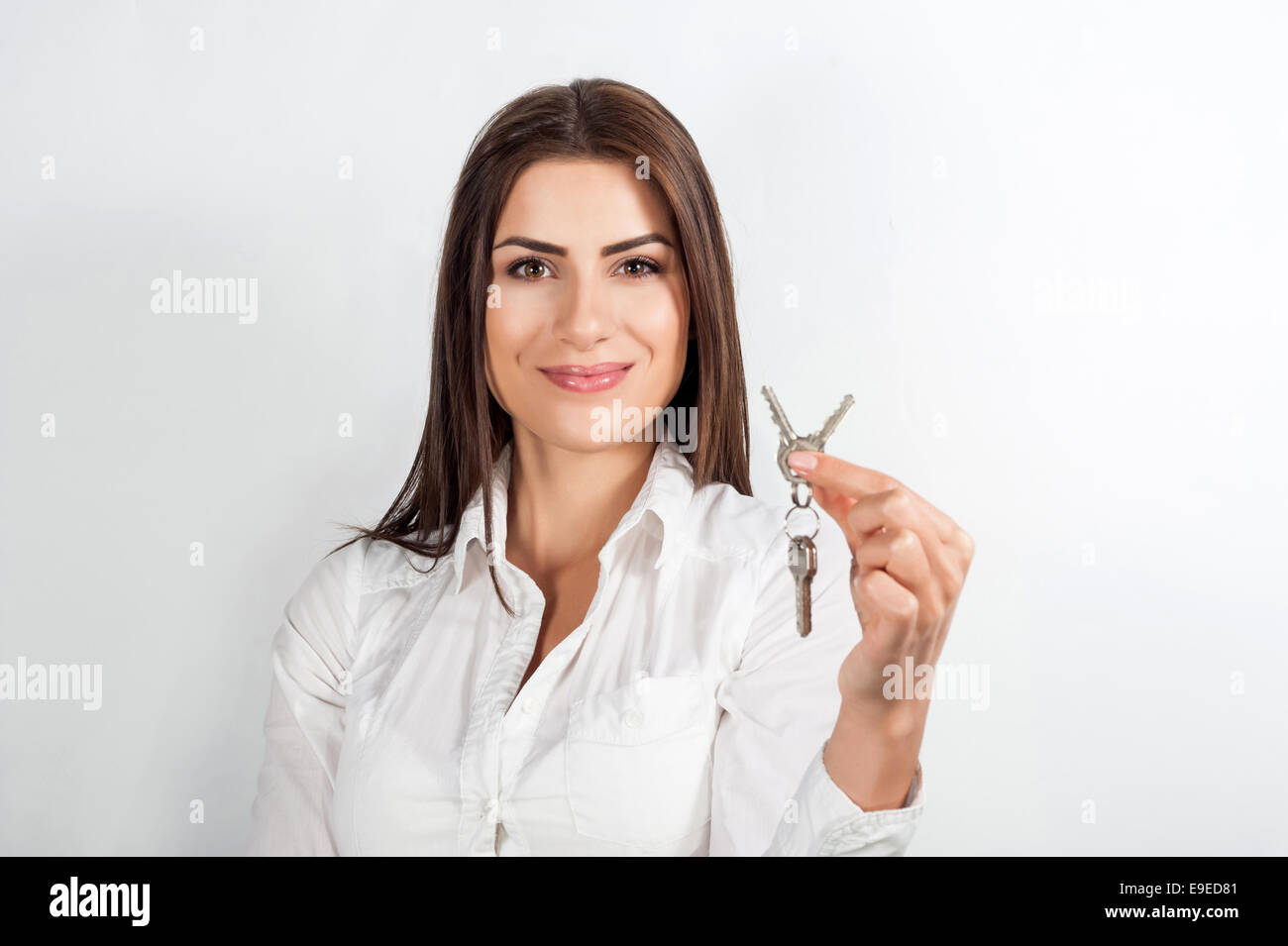 Young happy smiling business woman or real estate agent showing keys from new house, isolated over white background Stock Photo