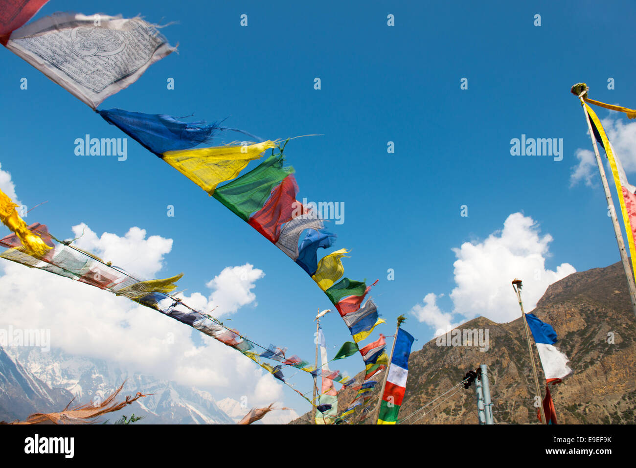 Colorful flags on a Annapurna Circuit - most popular tourists trek in Himalayan mountain massive in Nepal. - Stock Image