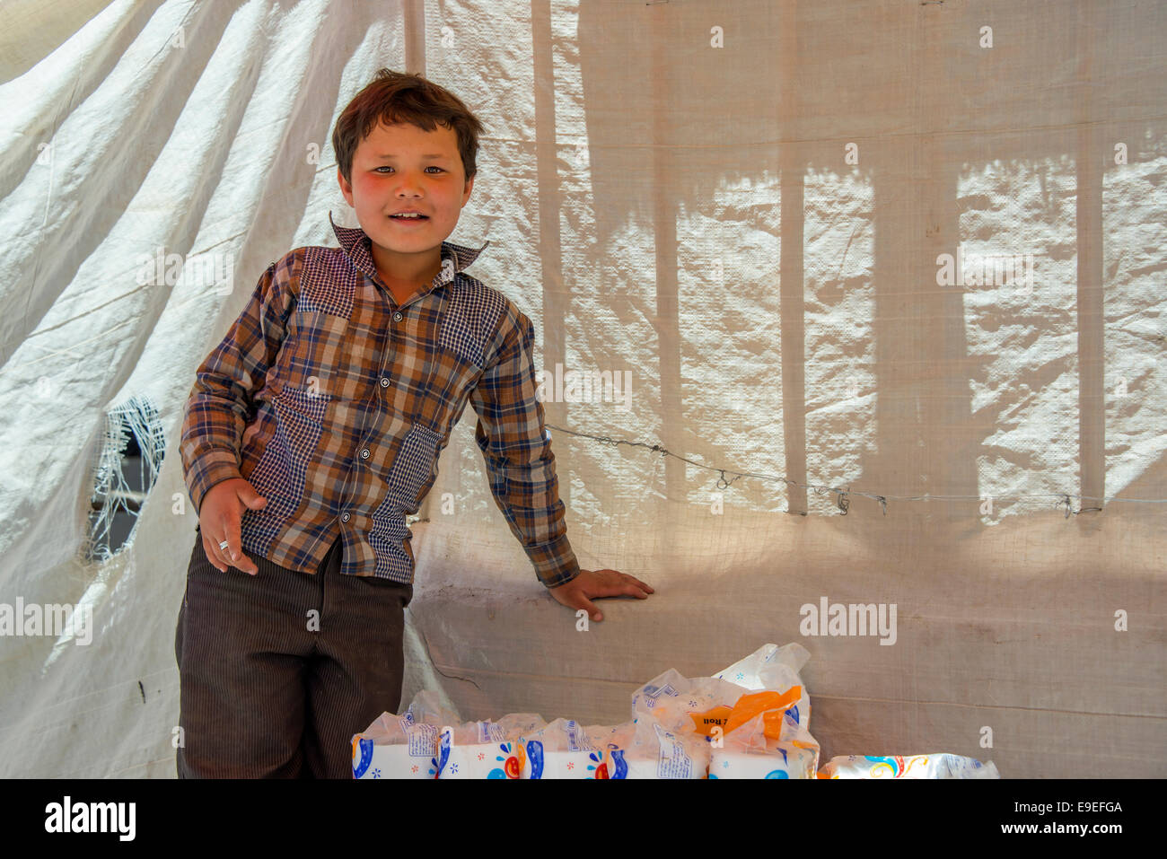Young Afghan refugee boy, selling toilet tissue, Kerman, Iran - Stock Image