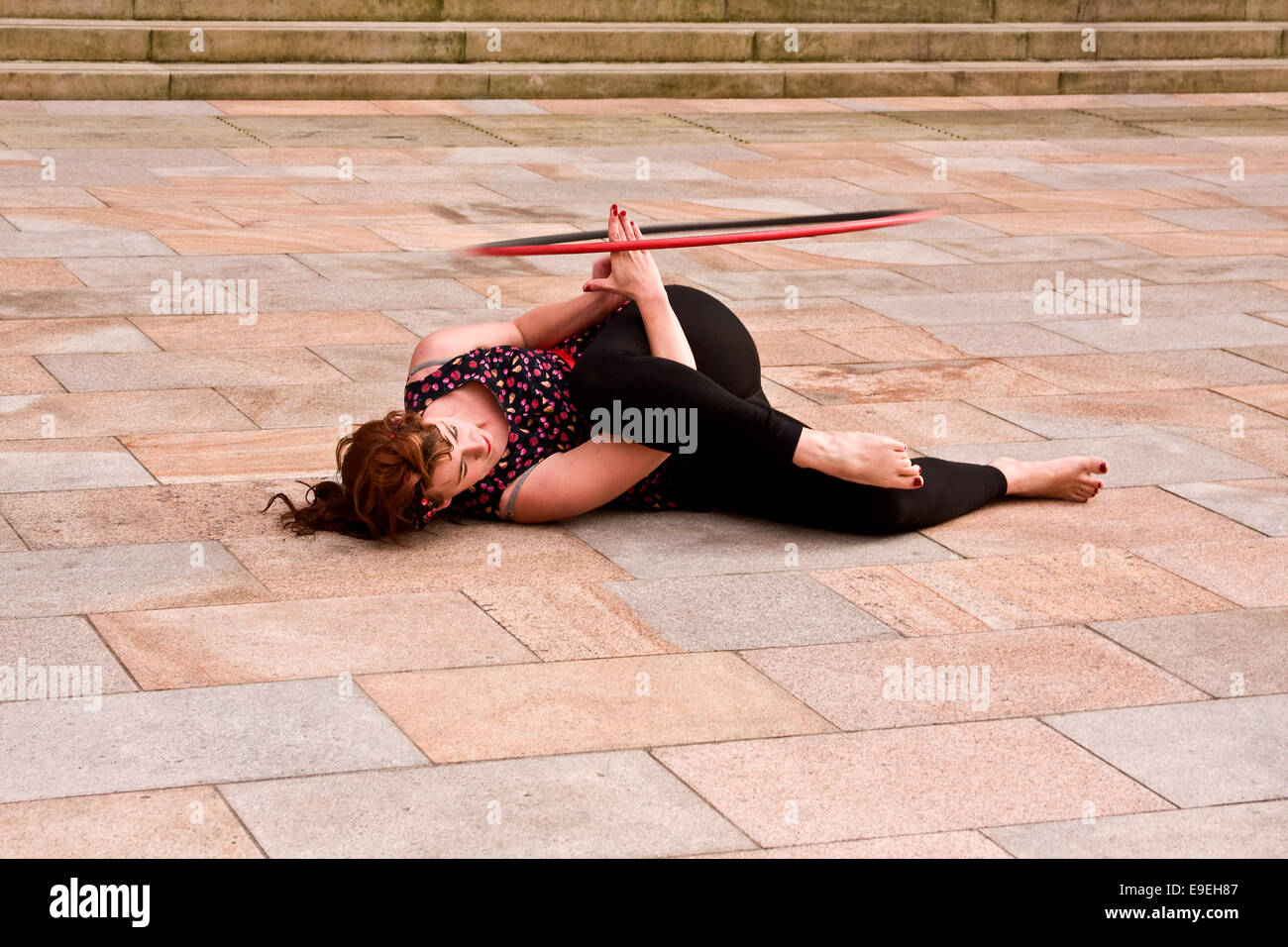 Claire Nicoll Hula Hoop dancing on a cold and windy October afternoon at the front entrance of the Caird Hall in - Stock Image