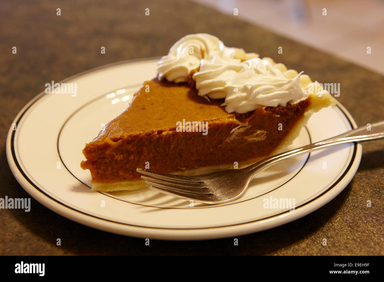 slice of mass produced pumpkin pie with cream in a cafe - Stock Image