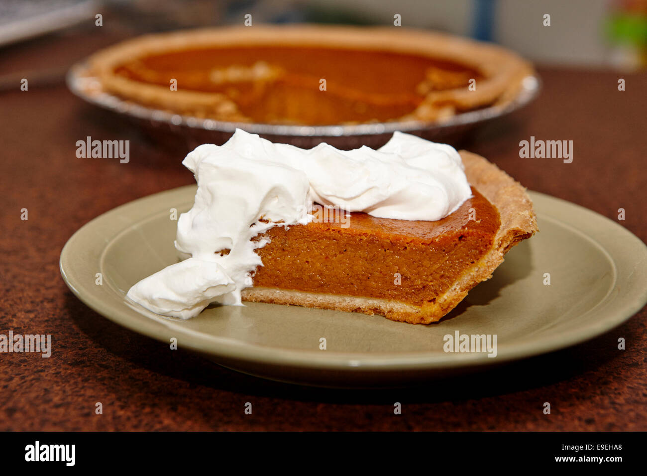 slice of mass produced pumpkin pie with whipped cream - Stock Image