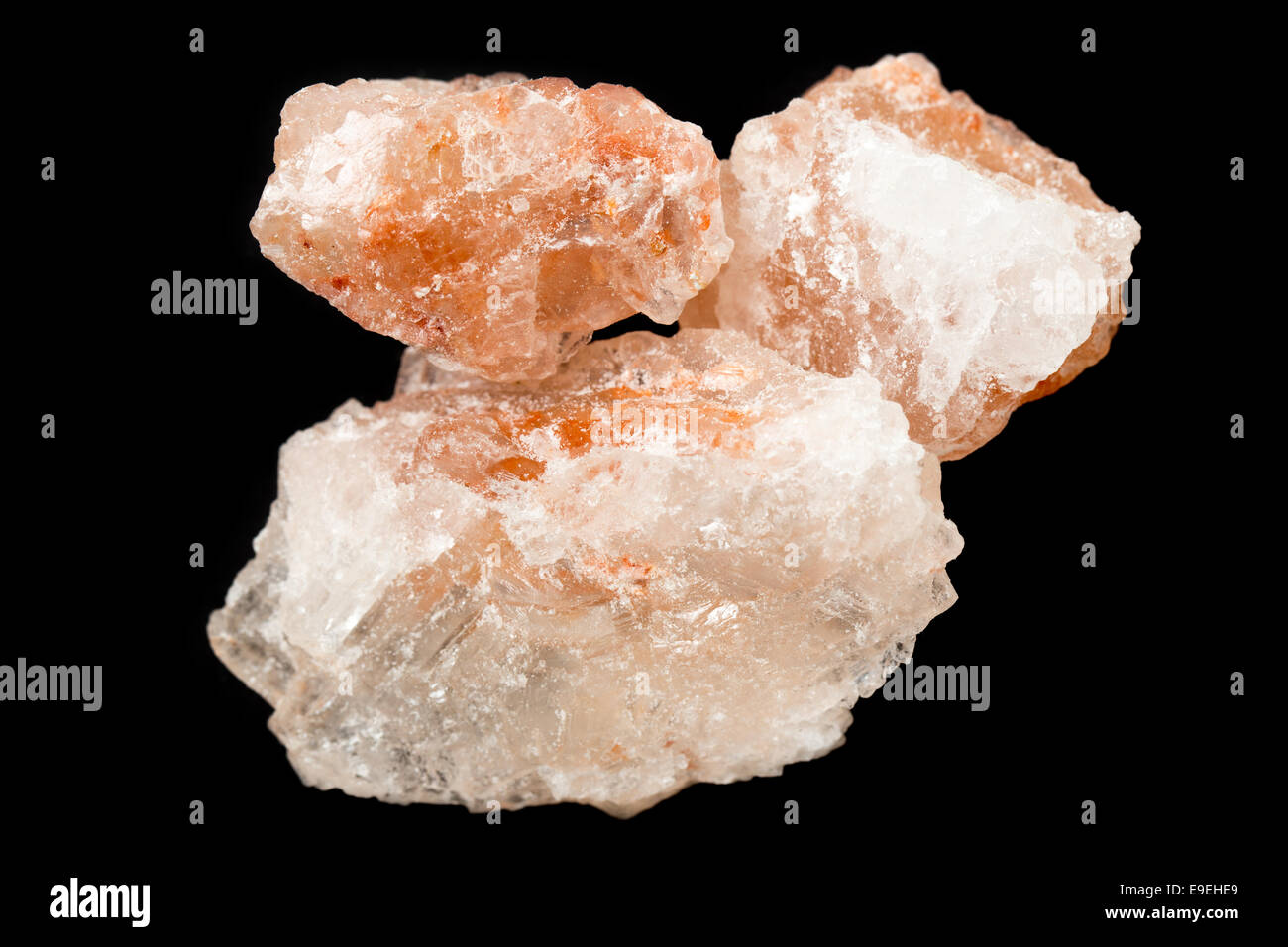 Crystalline Himalayan pink rock salt, a fashionable condiment, over a black background - Stock Image