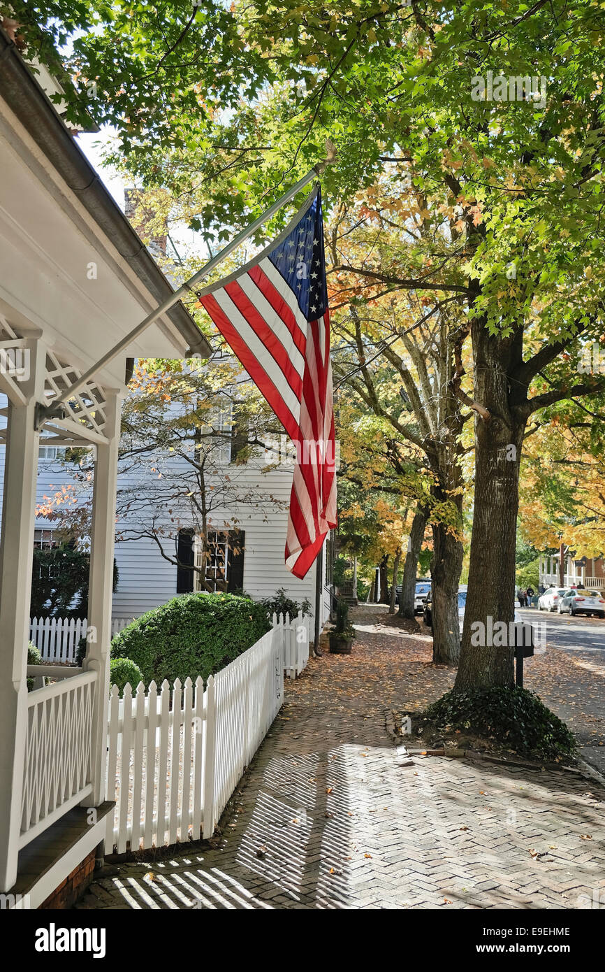 American flag off front porch in fall. Along S. Main Street in Old Salem, NC - Stock Image