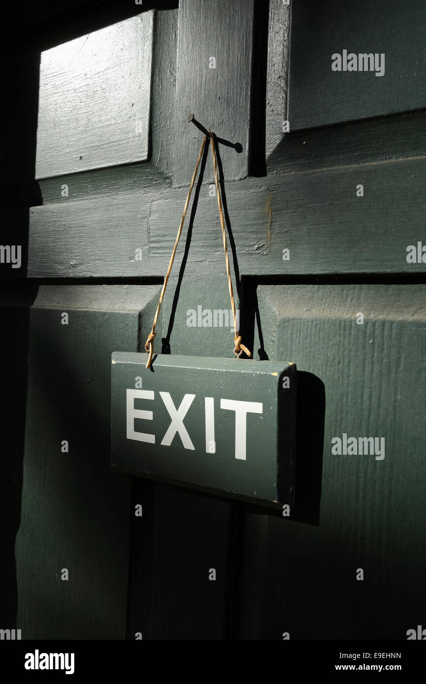 Exit sign on a door hanging on leather strap on a nail - Stock Image