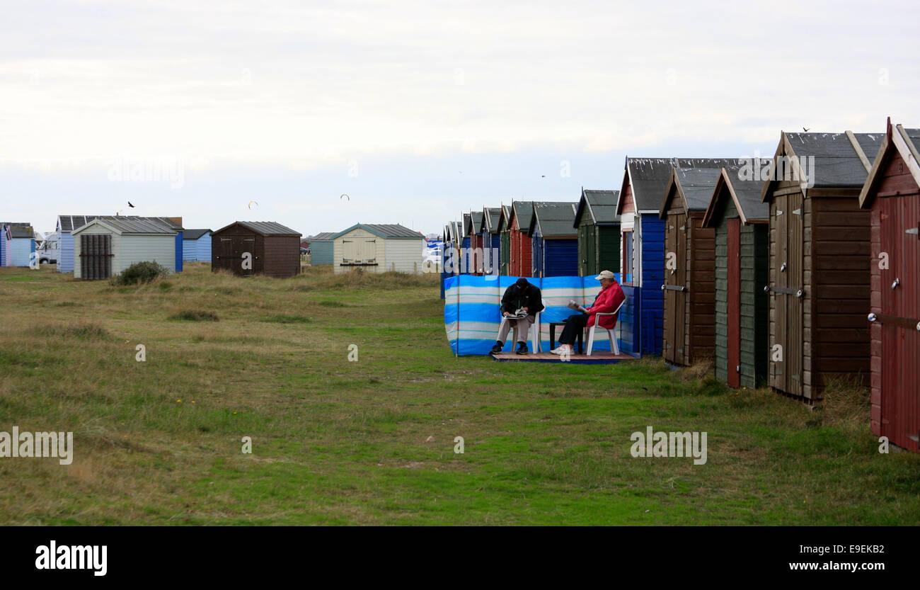 Sitting outside beach huts on Hayling Island sea front - Stock Image