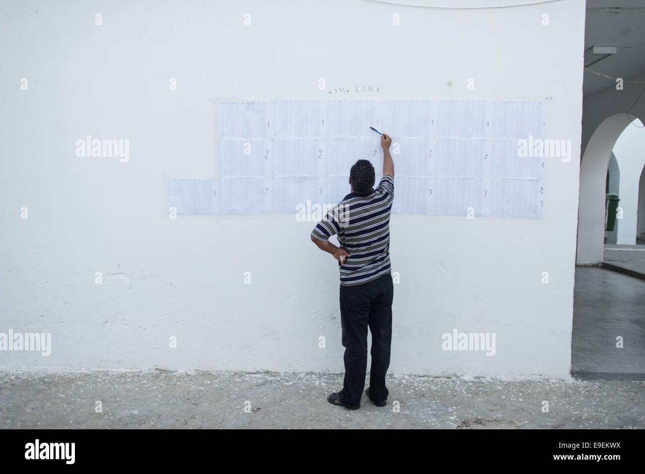 Tunis, Tunisia. 26th Oct, 2014. An Electoral worker checks information at a polling station in Tunis, capital of - Stock Image