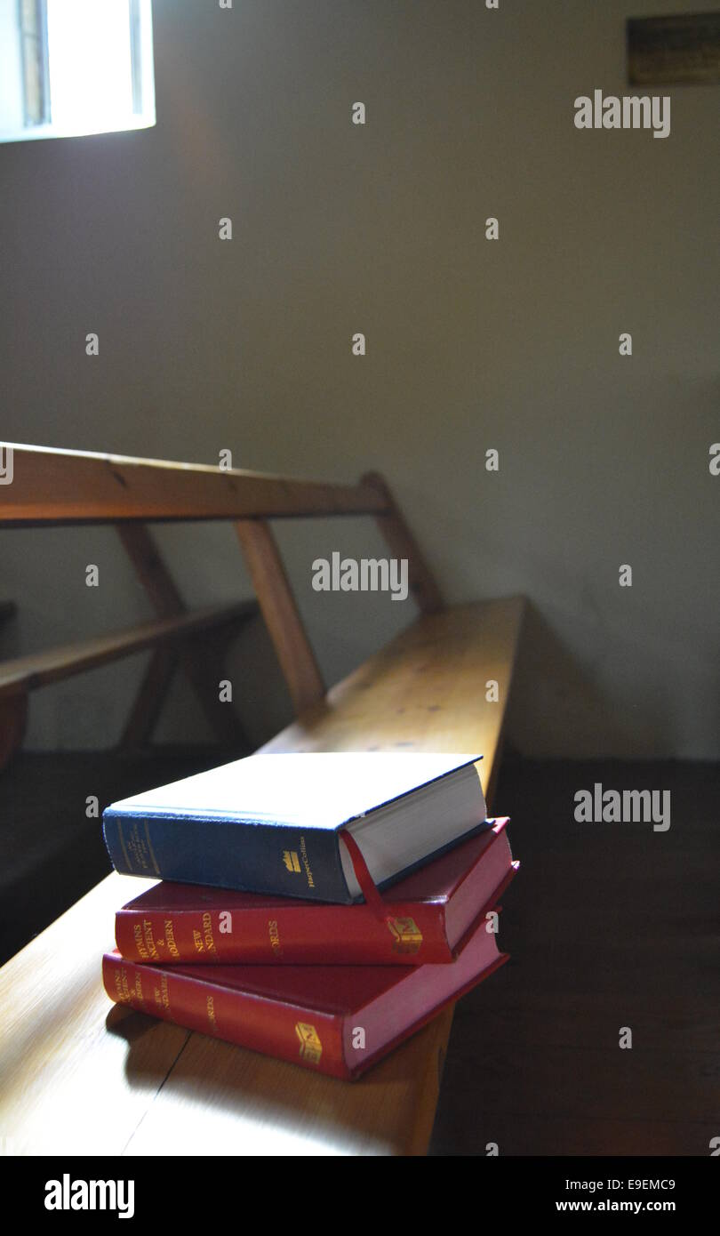 A stack of books on a church pew bathed in natural light - Stock Image