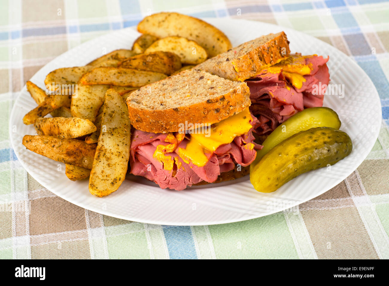 Corned Beef Sandwich Mustard Roasted Potatoes and Pickle on Plate - Stock Image