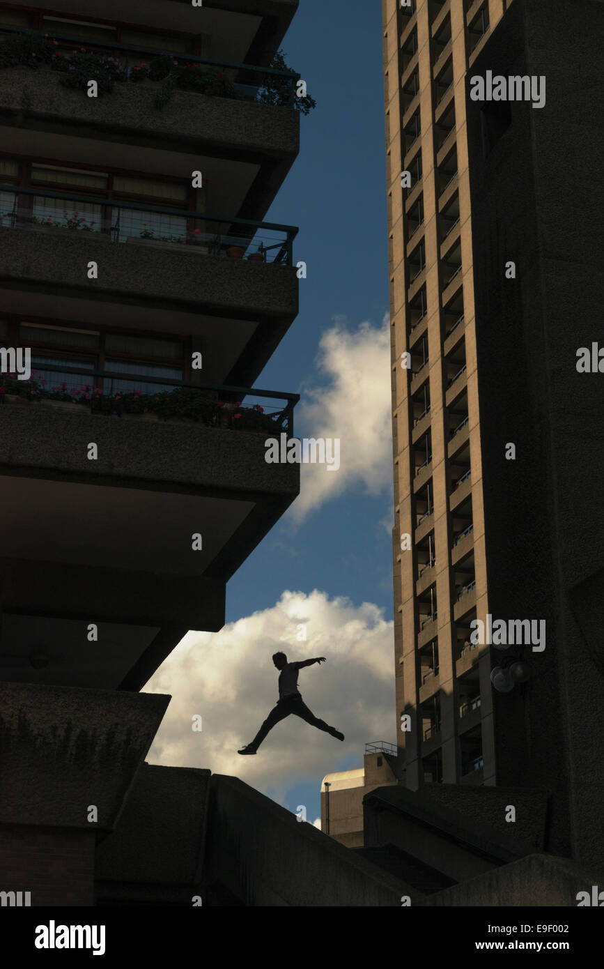 Decisive moment - silhouette of male parkour traceur leaping - Stock Image