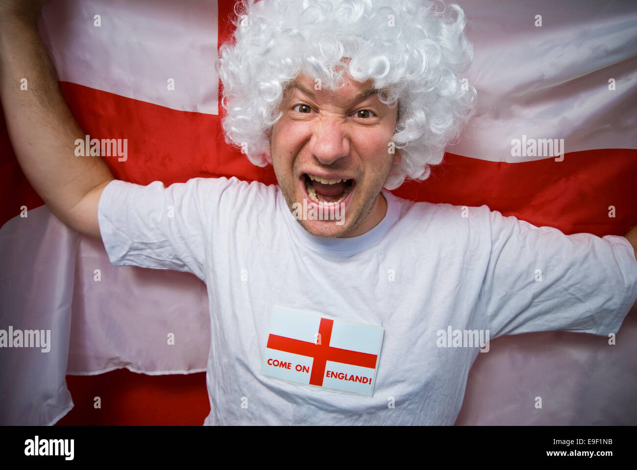 an english football fan waives a st georges flag with a white wig and t shirt - Stock Image