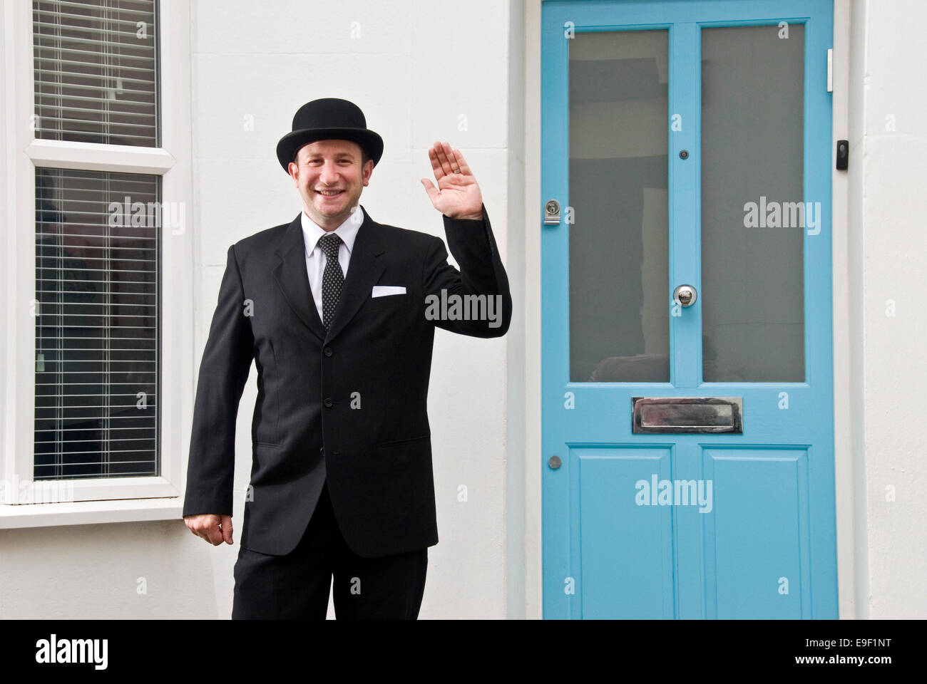 A man dressed as Mr Ben in a black suit and bowler hat stands ...