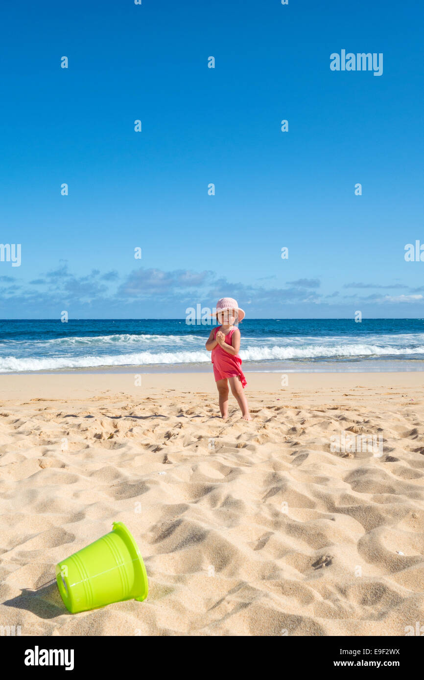Toddler girl at the beach with green bucket, Kuaui island - Stock Image