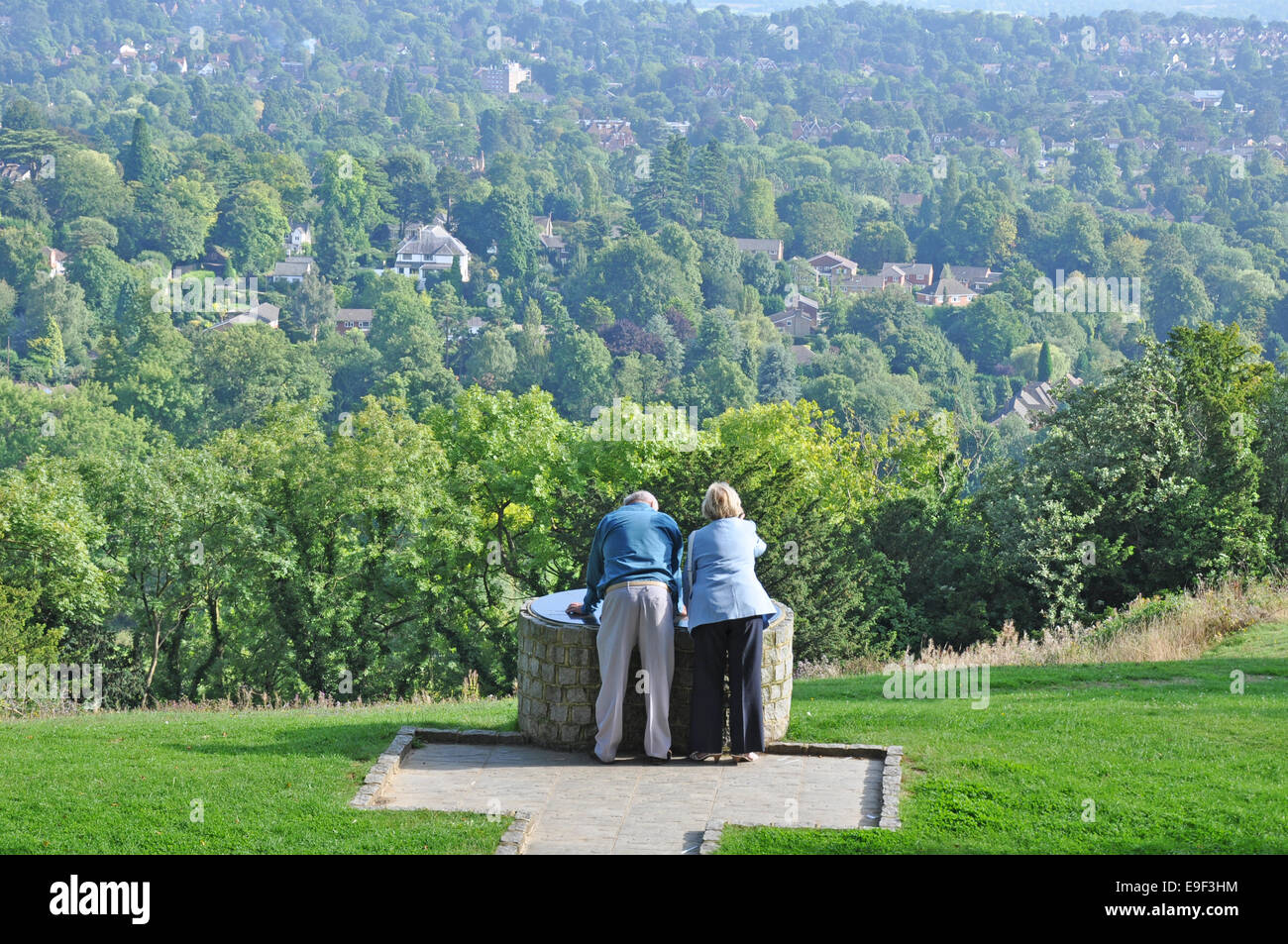 An elderly couple overlooking the locality at a viewpoint on Reigate Hill, Surrey, England, UK. - Stock Image