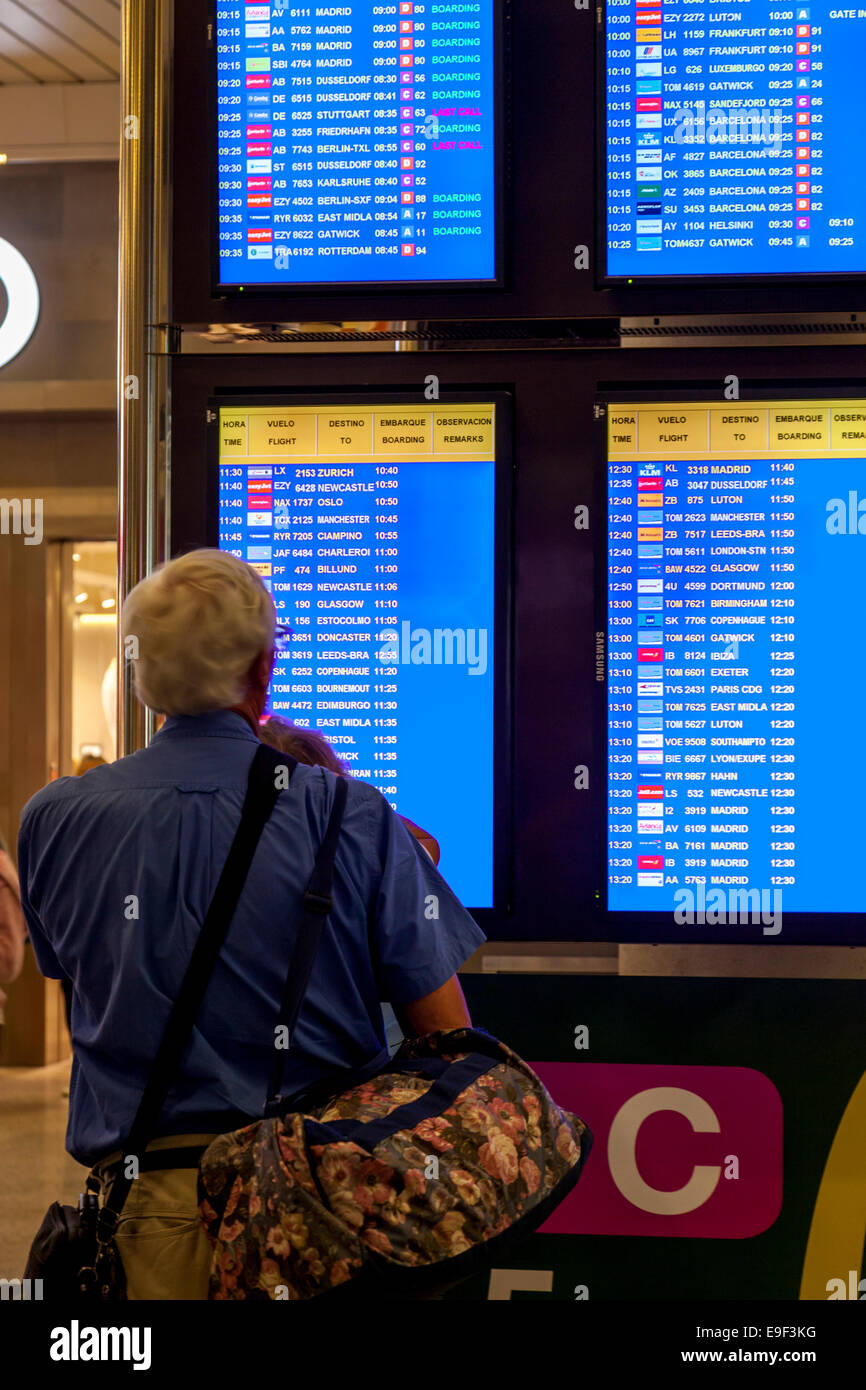 Man Looking At The Flight Departure Screens, Palma Airport, Palma de Mallorca - Spain - Stock Image