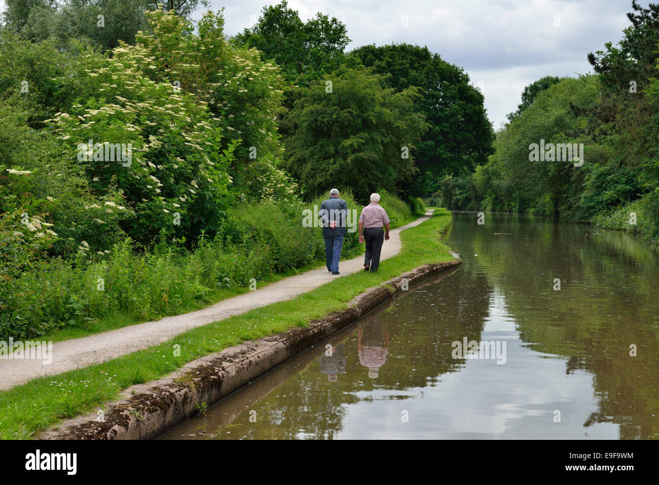Two men walking along the canal towpath, West Midlands, United Kingdom - Stock Image