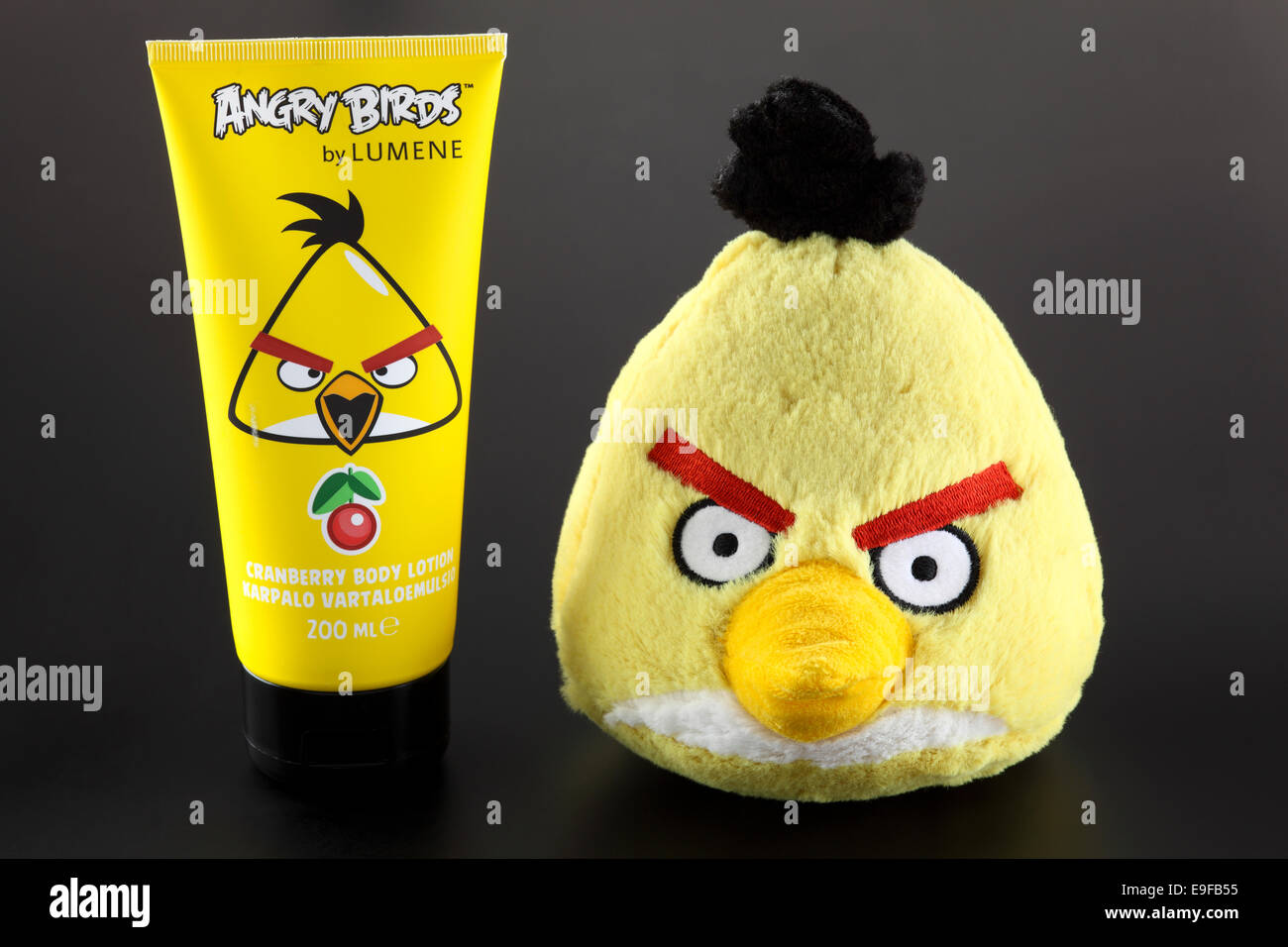 Yellow Angry Birds soft toy and Angry Birds by LUMENE Cranberry Body Lotion on black background. - Stock Image