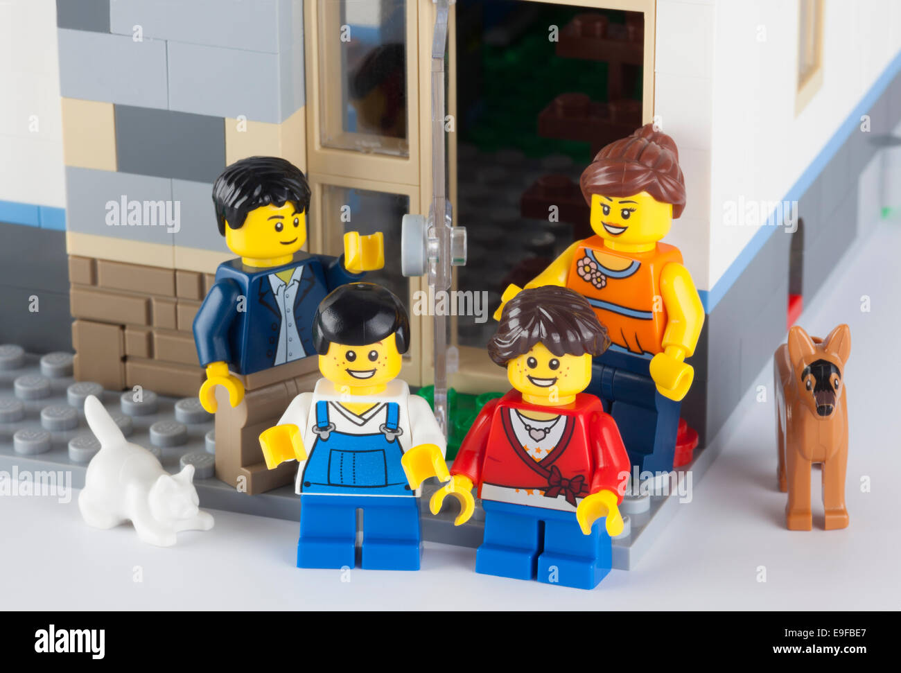 Tambov, Russian Federation - January 12, 2014 Happy LEGO family standing near his home with pets. - Stock Image