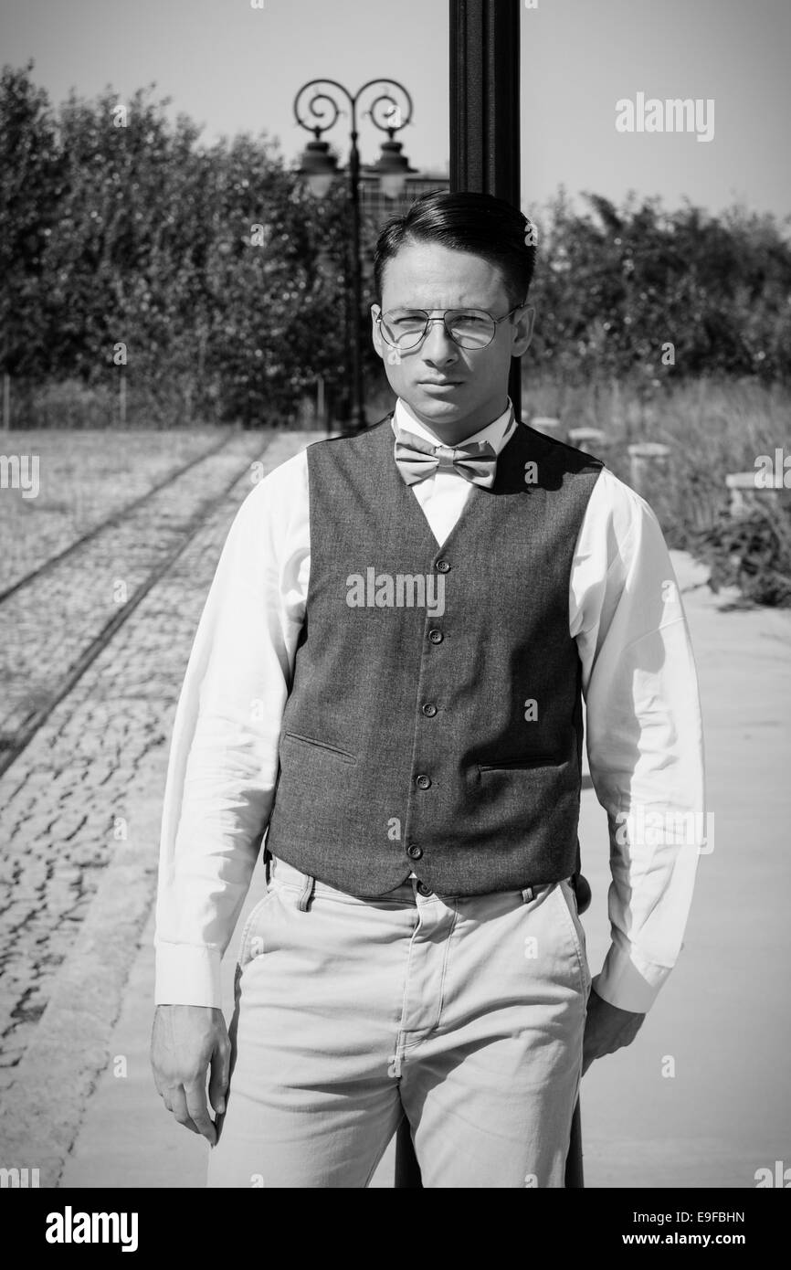 Man in vest and bowtie standing by the railway leaning against lamppost in old vintage town in black and white - Stock Image