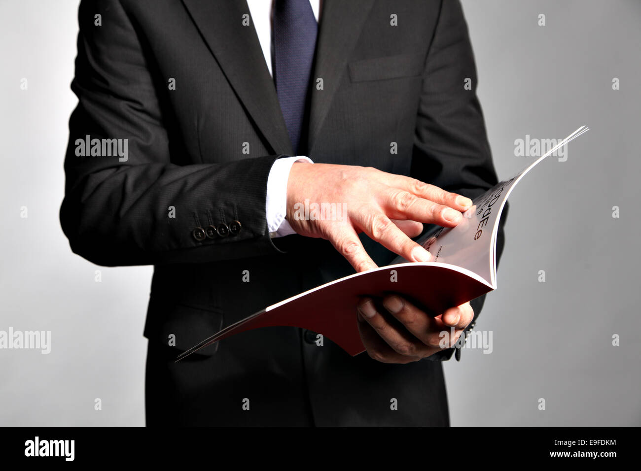 Businessman holds a booklet - Stock Image