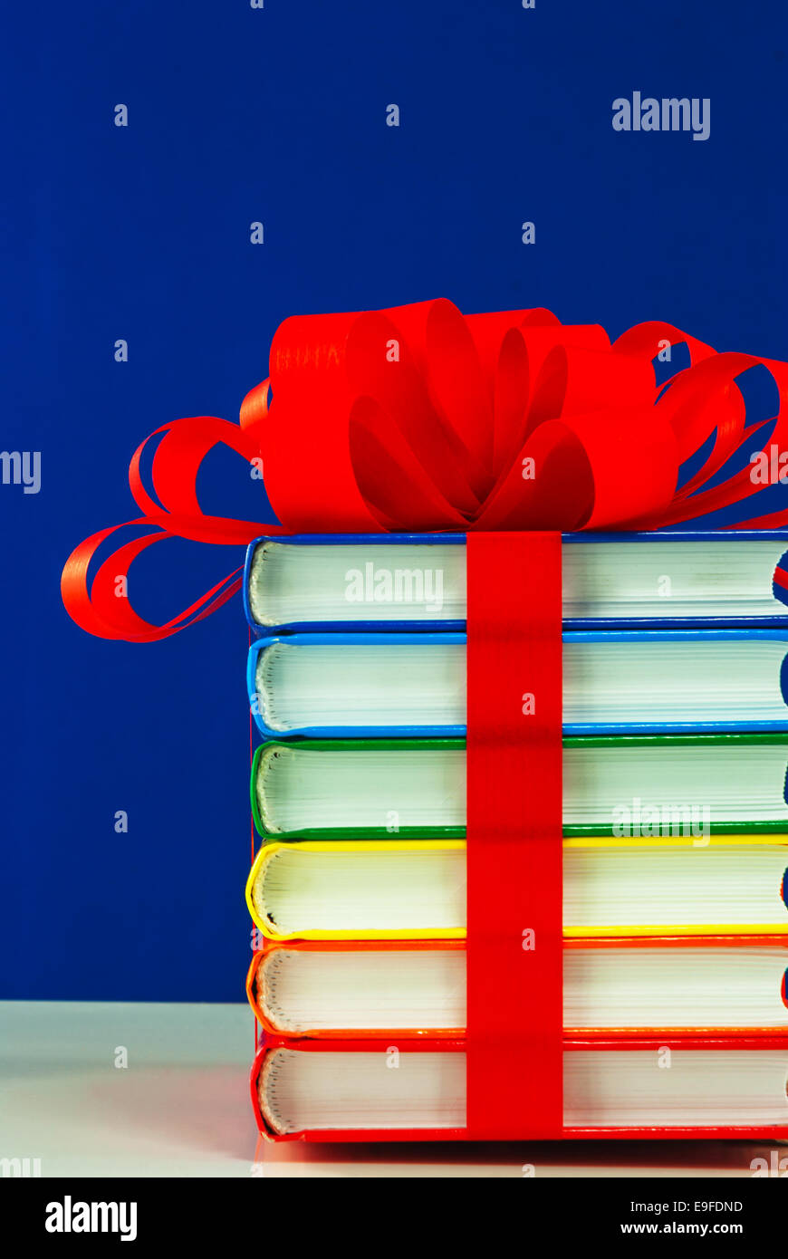 Stack of colorful books tied up with ribbon - Stock Image