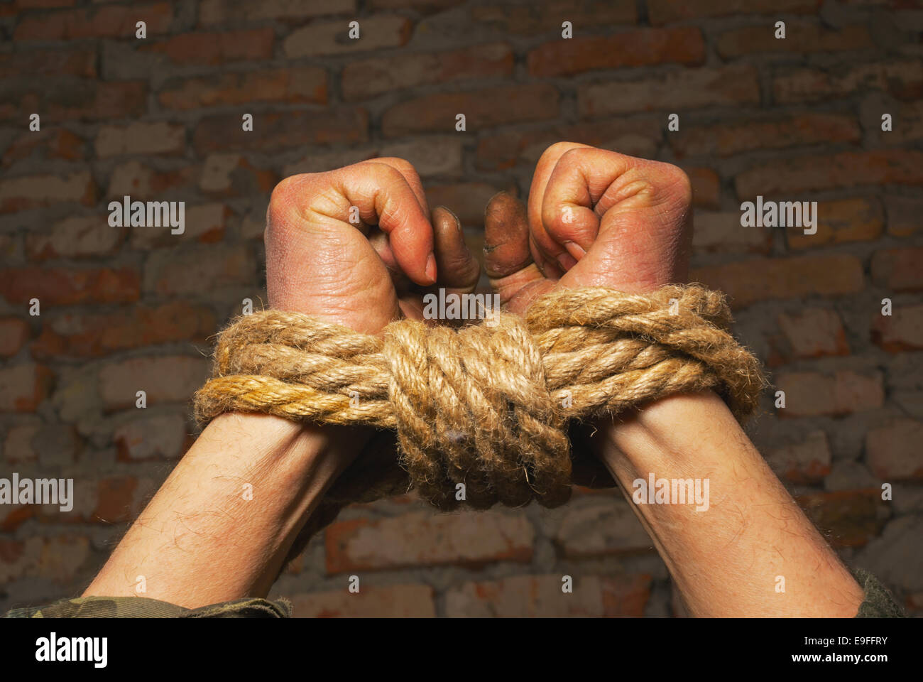 Hands tied up with rope - Stock Image
