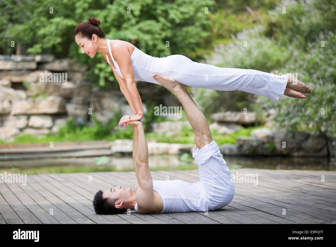 Young couple doing yoga - Stock Image