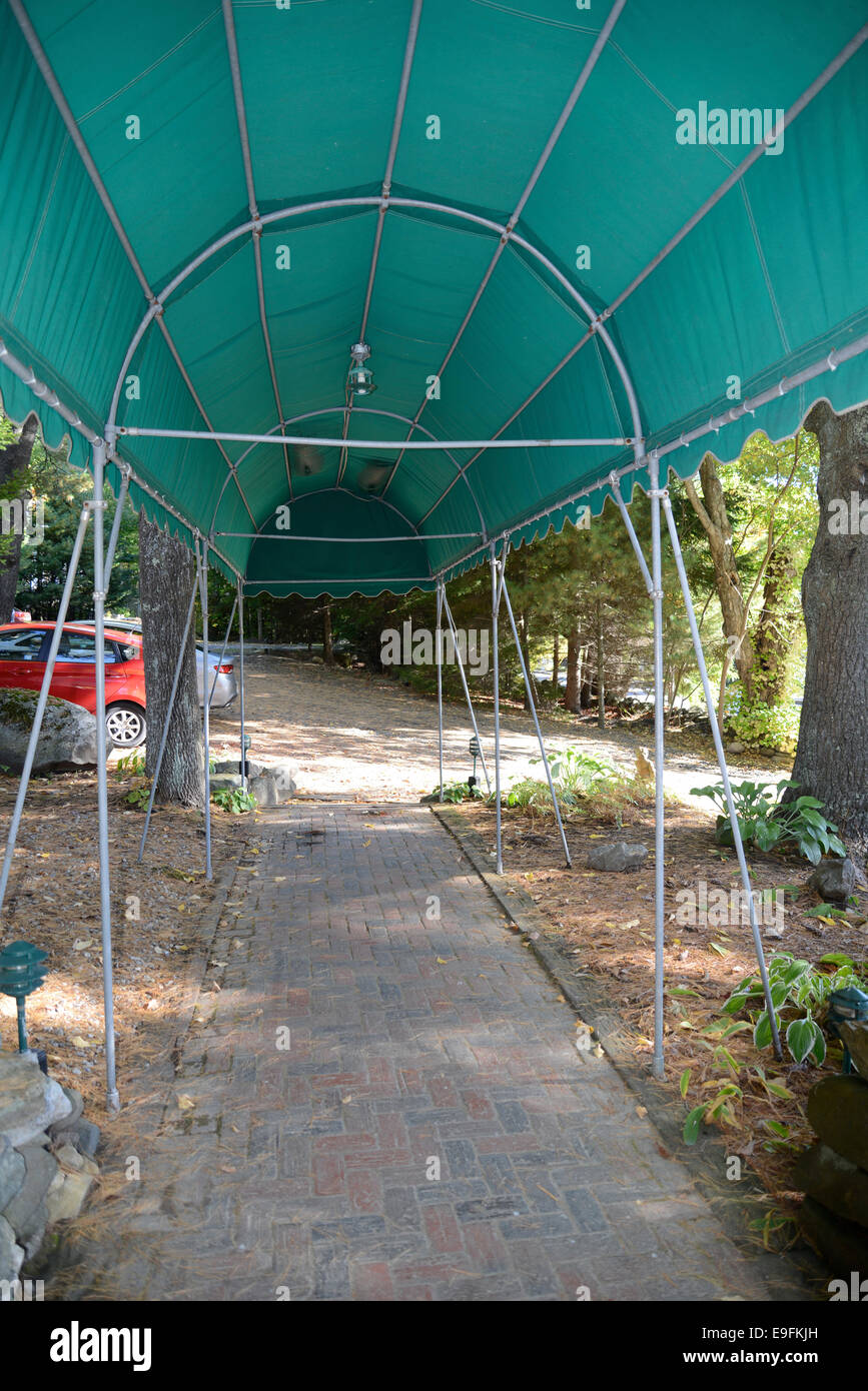 a green canvas canopy covers an outdoor brick walkway Stock Photo