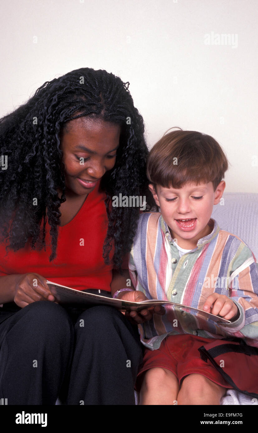 young woman reading to boy - Stock Image