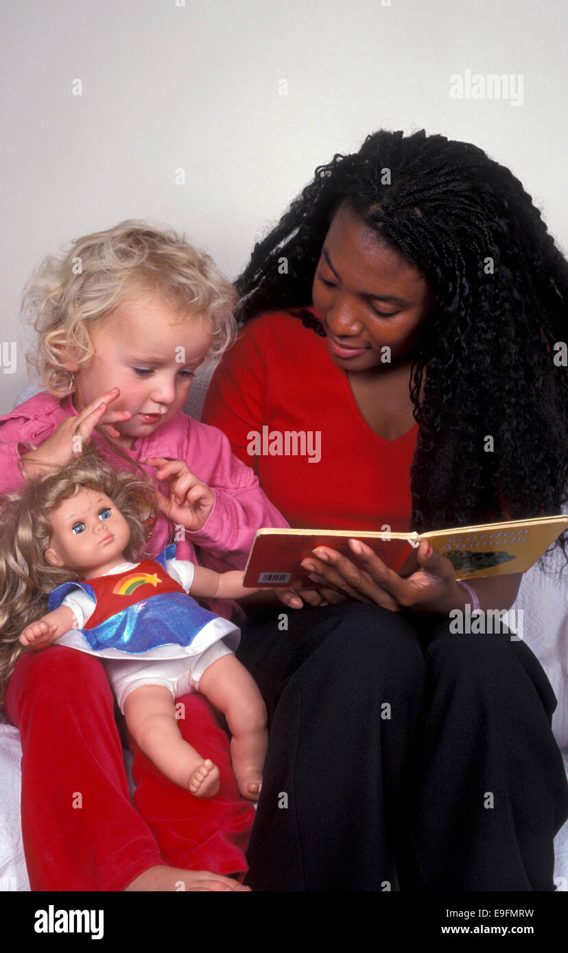 young woman reading to little girl - Stock Image
