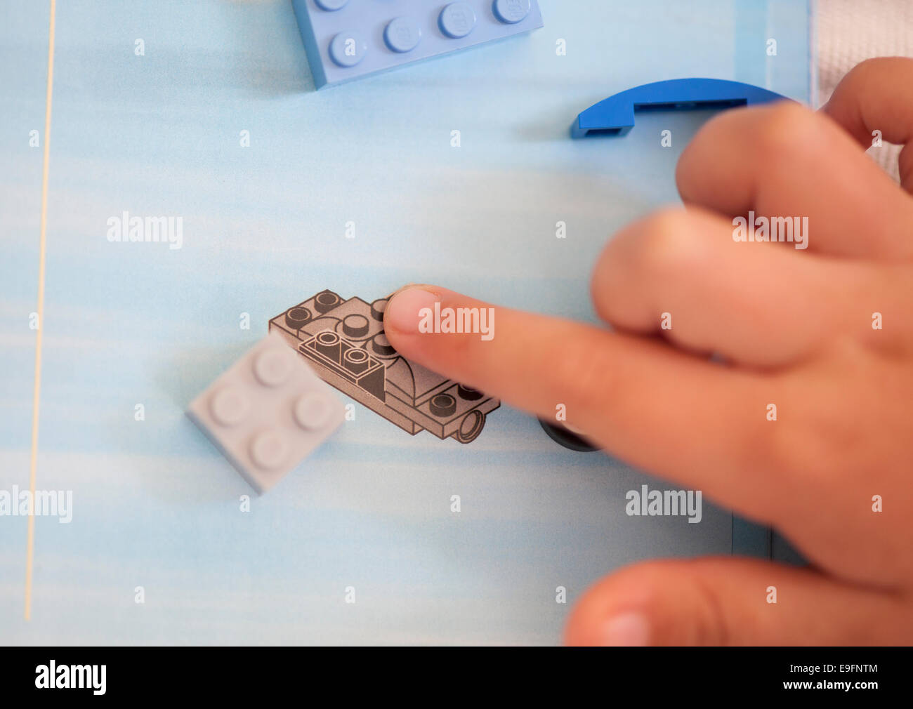Paphos, Cyprus - December 19, 2013 Children's fingers showing on the Lego instructions. - Stock Image