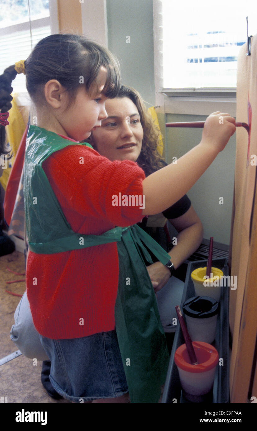 nursery school assistant painting with child - Stock Image