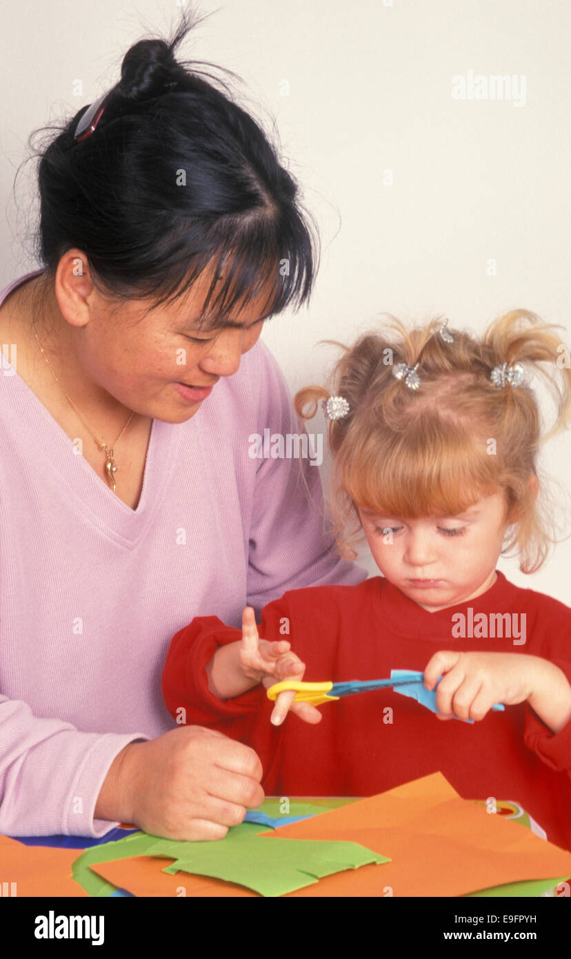 woman supervising young girl cutting paper - Stock Image