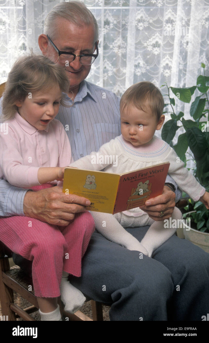 traditional Grandpa reading to baby and child - Stock Image