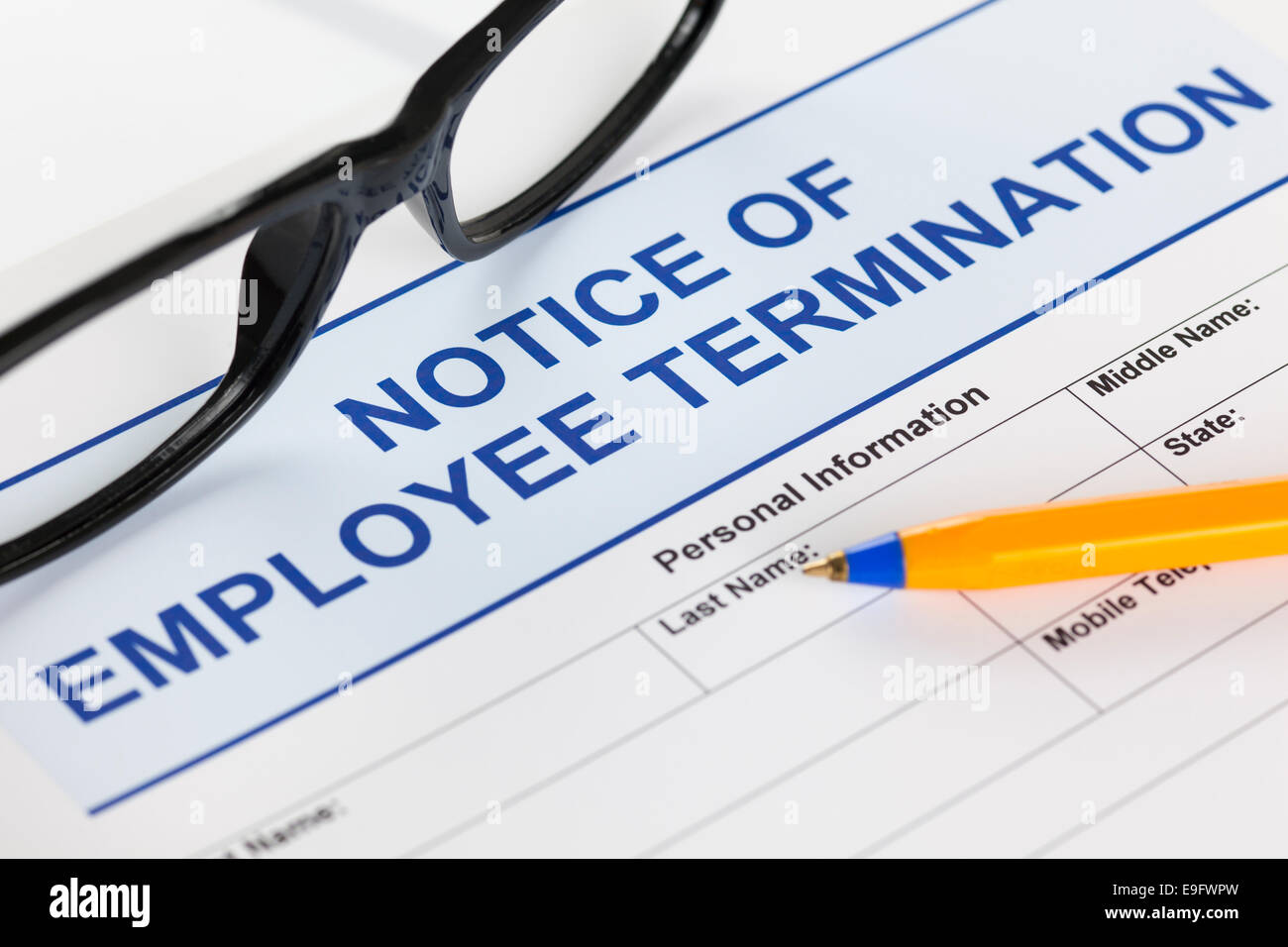 Notice of employee termination with glasses and ballpoint pen. - Stock Image