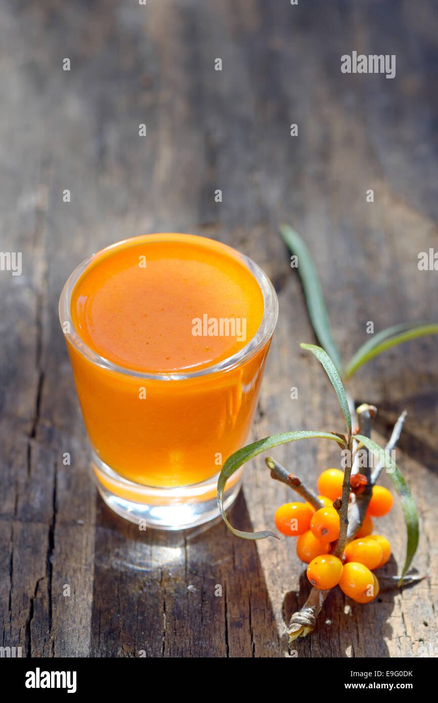 Sea buckthorn juice and berries isolated on wooden background. Natural detox. - Stock Image