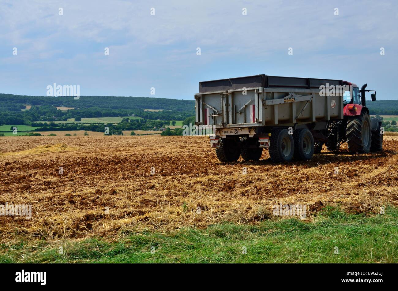 Lying on ochre-yellow colour land, a truck is resting after harvesting days ploughing the land. In the center of Stock Photo
