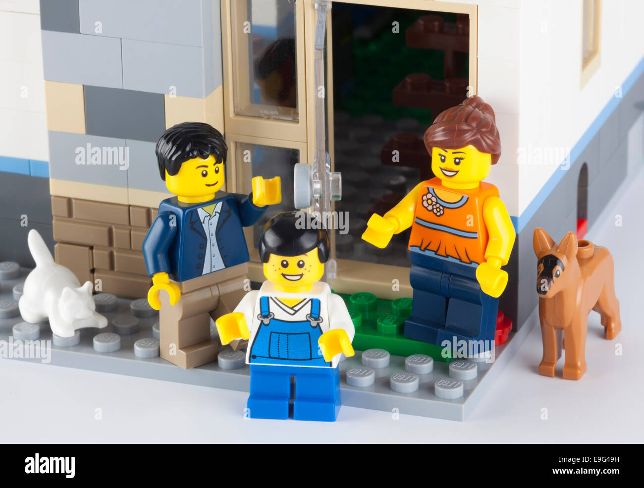 Tambov, Russian Federation - January 08, 2014 Happy LEGO family standing near his home with pets. - Stock Image