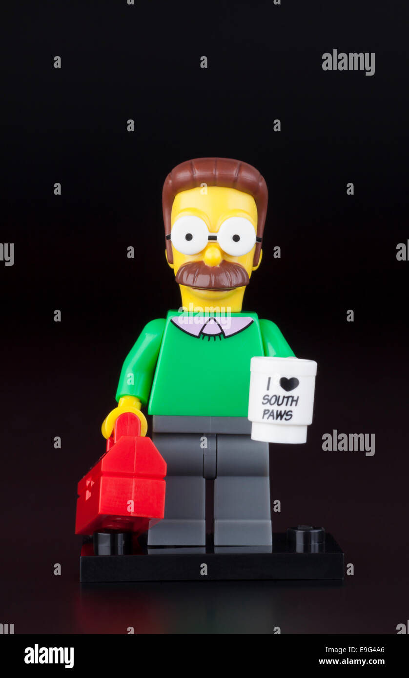 Tambov, Russian Federation - April 30, 2014 LEGO Ned Flanders minifigure with mug and red suitcase on black background. - Stock Image