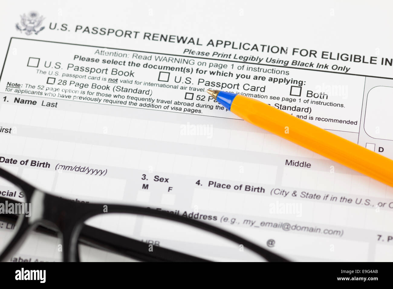 U.S. passport renewal application for eligible individuals with ballpoint pen and glasses. - Stock Image