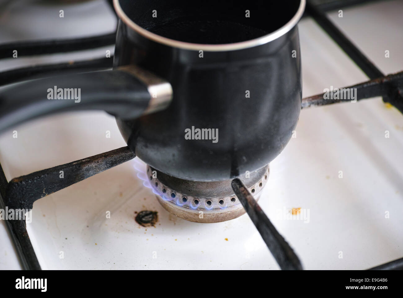 Pot on flame burning of old dirty gas cooker. - Stock Image