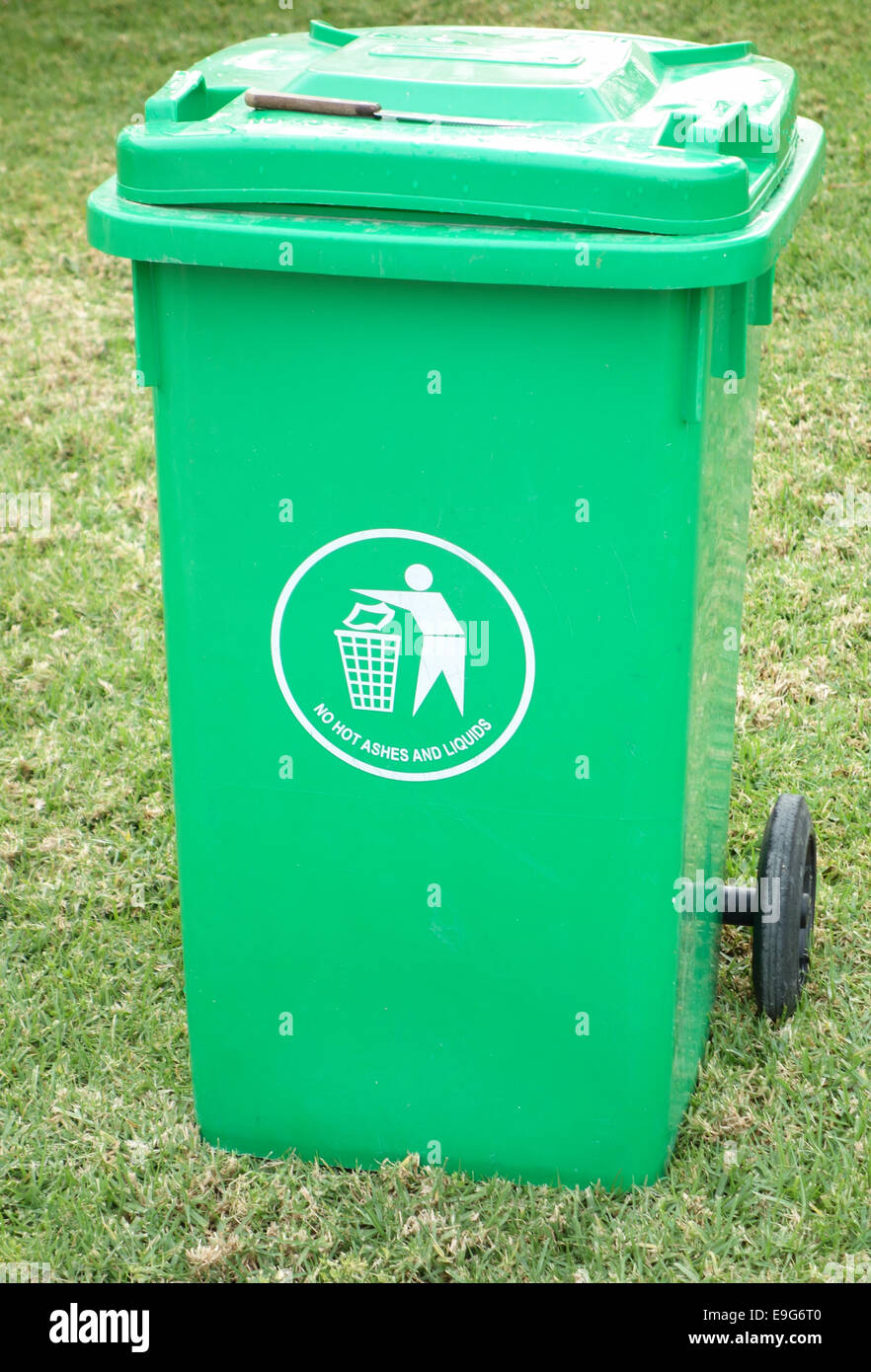 Outdoor green garbage can with knife on it top - Stock Image