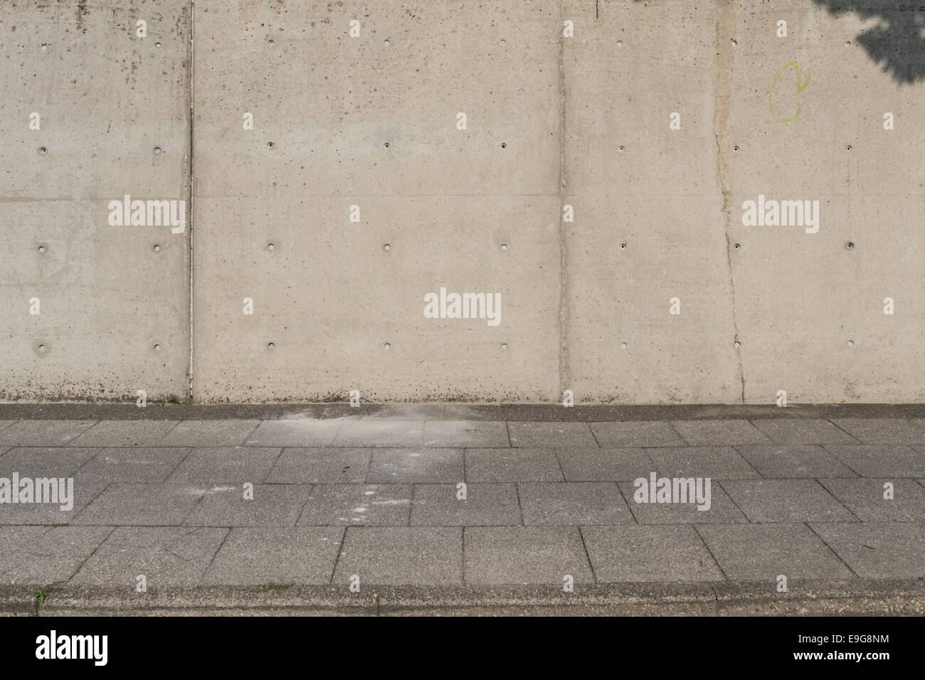 Large concrete wall with sideway in front - Stock Image
